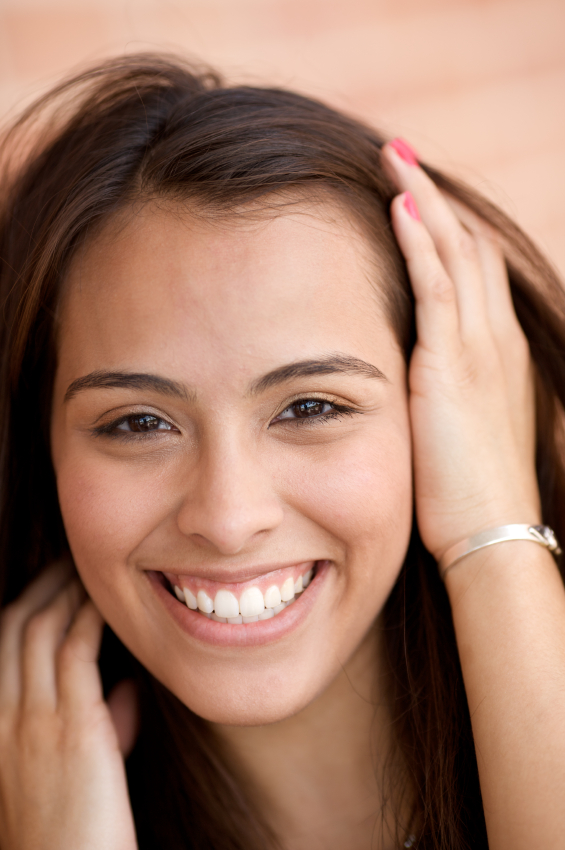 Young woman smiling about her tooth repaired with composite bonding by her dentist in Chandler, AZ.